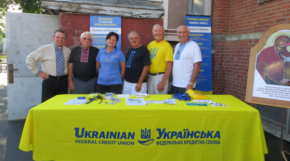 Community members stand with UFCU staff by booth