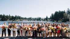Youth stand by water for baptism holding flowers
