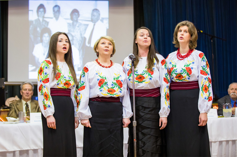 Group of four female singers sing a song