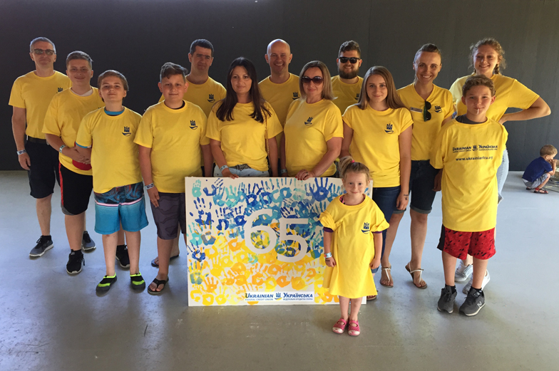 Group in yellow t-shirts stand on a stage