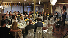 Photo of the dinner event and speaker speaking