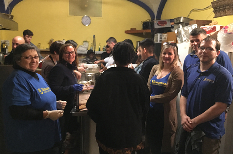 Volunteers serving food and posing for photo