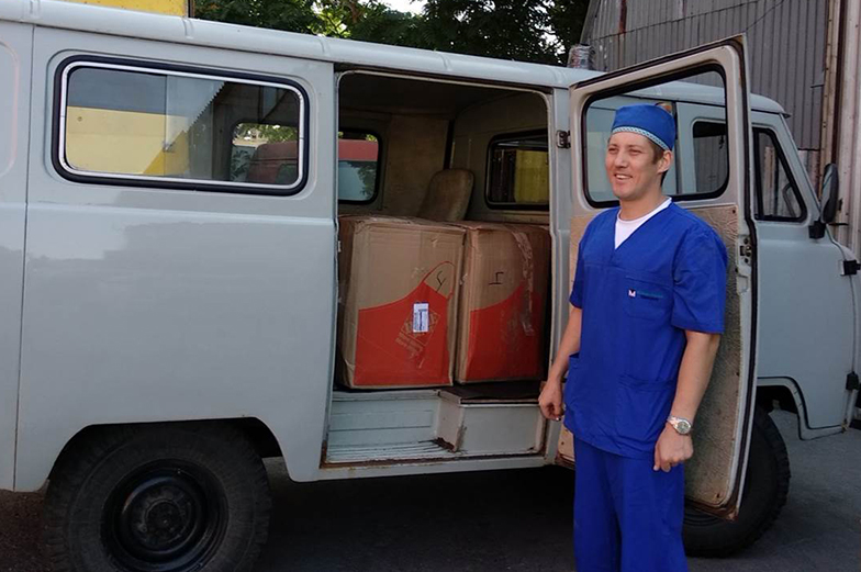Supplies in a van with guy posing next to it