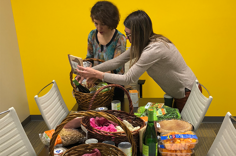 Two women preparing a meal basket