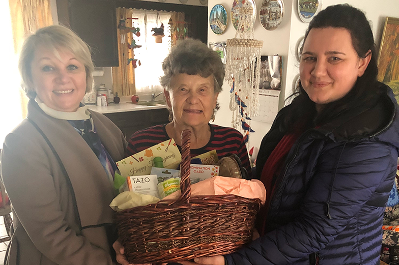 Three women holding a meal basket