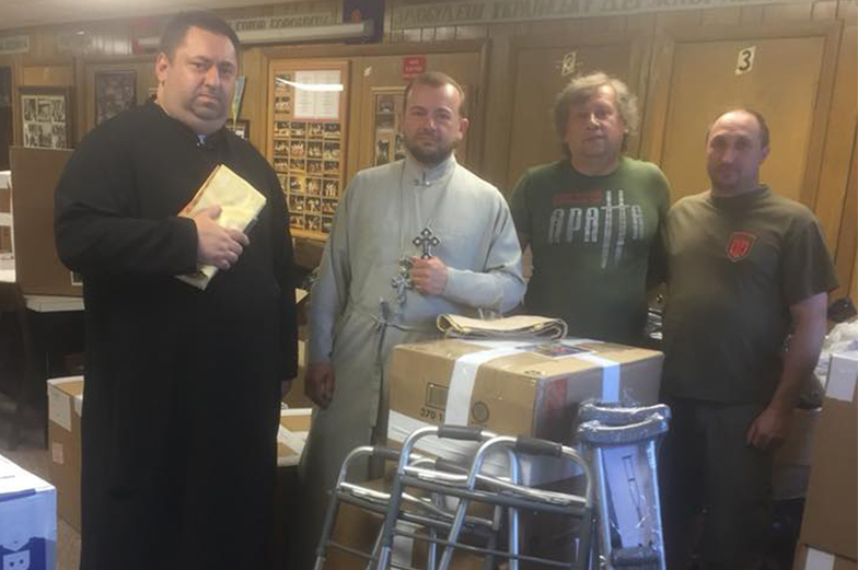 Two priests and two guys posing with donation boxes
