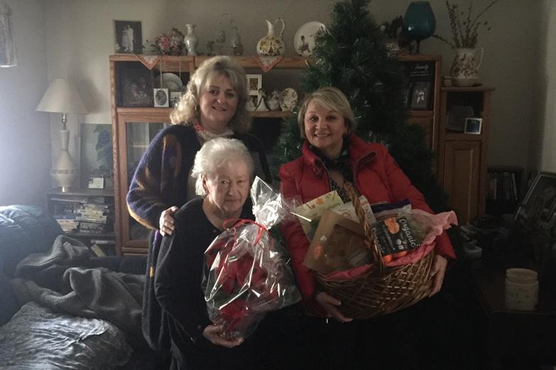 Two adult females delivering meal basket to older female