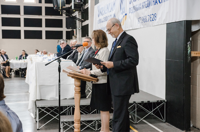 adults standing at podium