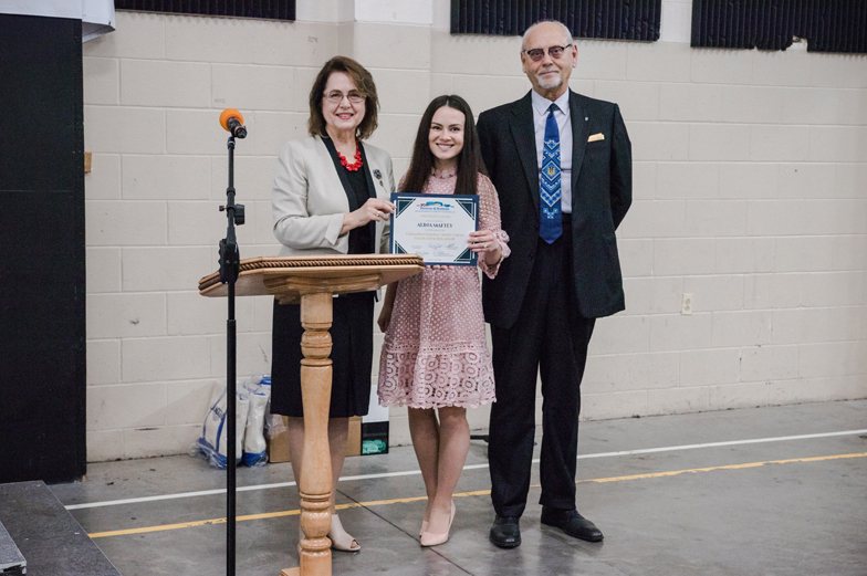 three adults standing, one receives certificate