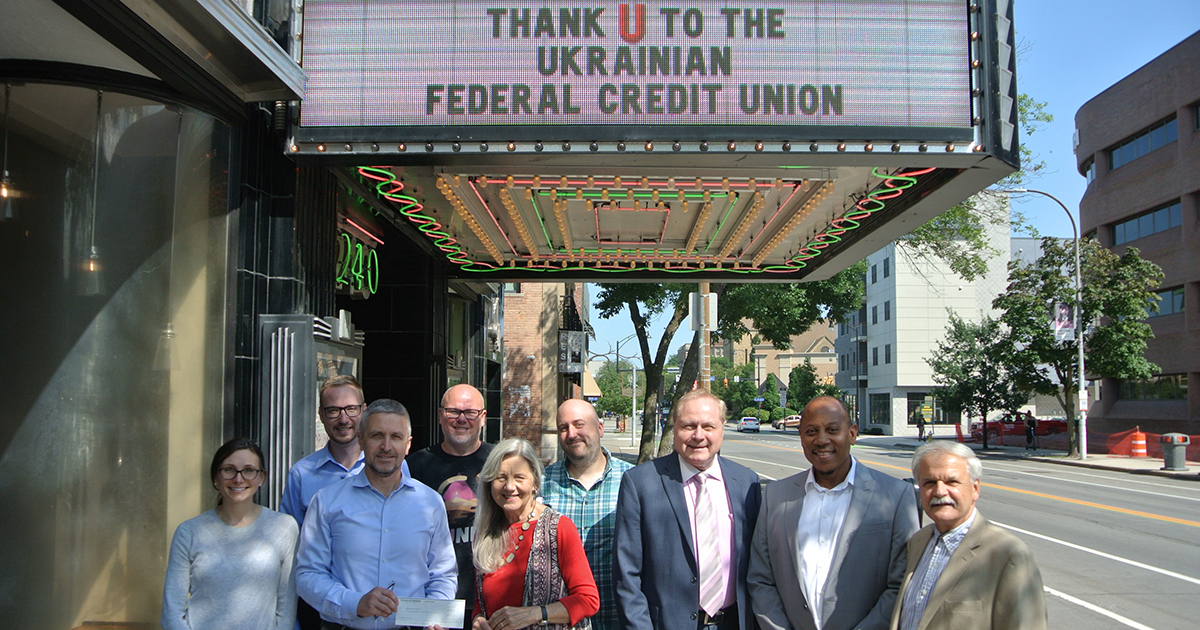 Group of adults standing, smiling under marquee